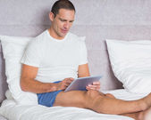Cheerful man using tablet pc on bed — Stock Photo