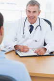 Cheerful doctor prescribing drug to his patient — Stock Photo