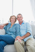 Middle aged couple sitting on the couch — Stock Photo