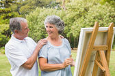 Happy retired woman painting on canvas with husband — Stock Photo