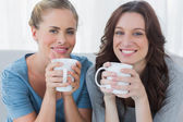 Friends having coffee and looking at camera — Stock Photo