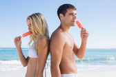 Happy young couple eating ice creams — Stock Photo