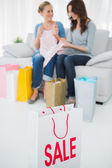 Friends with purchase and shopping bag on foreground — Stock Photo