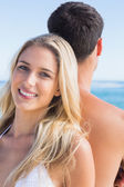 Pretty blonde smiling and leaning against her boyfriend — Stockfoto