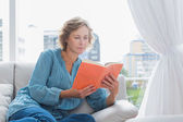 Cheerful blonde woman sitting on her couch reading a book — Stock Photo