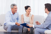 Salesman and clients talking and laughing together on sofa — Stock Photo