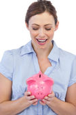 Astonished businesswoman posing with piggy bank — Stock Photo