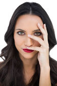 Dark haired woman with red lips hiding her face — Stock Photo