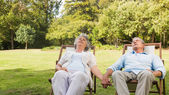 Mature couple relaxing on sun loungers — Stock Photo