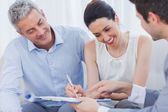 Smiling woman sign on a contrat with her partnership on sofa — Stock Photo