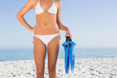 Sexy female body in white bikini holding fins — Stock Photo