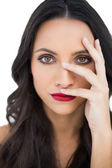 Dark haired model with red lips hiding her face — Stock Photo