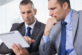 Focused businessmen analyzing documents on their tablet — Stock Photo