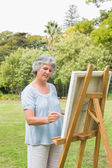 Happy retired woman painting on canvas — Stock Photo
