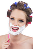 Smiling model in hair curlers posing while shaving — Stock Photo