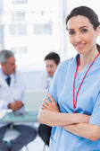 Nurse crossing arms with her colleagues behind — Stock Photo