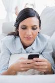 Mujer de cabello oscuro tirado en el sofá enviando mensajes — Foto de Stock