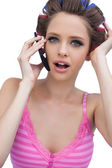 Sexy young model wearing hair rollers with phone — Stock Photo
