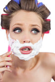Shocked young model in hair curlers posing with razor — Stock Photo