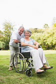 Happy mature woman in wheelchair with partner — Stock Photo