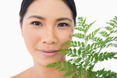 Relaxed sensual model with fern caressing her face — Stock Photo