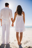 Attractive couple holding hands and watching the water — Stock Photo