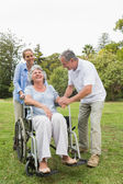 Retired woman in wheelchair with husband and daughter — Stock Photo