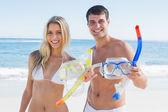 Aantrekkelijke paar tonen snorkeluitstappen en goggles naar camera — Stockfoto