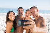 Cheerful friends taking pictures of themselves — Stock Photo