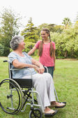 Happy granddaughter talking with grandmother in her wheelchair — Foto Stock