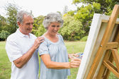 Content retired woman painting on canvas and talking with husban — Stock Photo