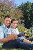 Dad and son with tablet pc smiling into the camera — Stock Photo