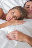 Happy woman lying on husbands chest in bed — Stock Photo