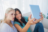 Two happy friends taking photo with tablet pc — Stock Photo