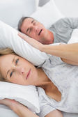 Tired wife blocking her ears from noise of husband snoring looki — Stock Photo