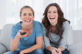Laughing women watching television — Stock Photo