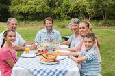 Multi generation family having dinner outside at picnic table — Stock Photo