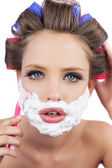 Model in hair curlers posing with shaving foam and razor in clos — Stock Photo