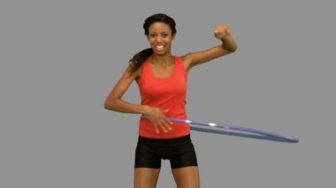 Woman playing with a hula hoop on grey screen in slow motion — Stock Video