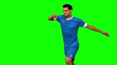 Football player kicking a football on green screen — Stock Video
