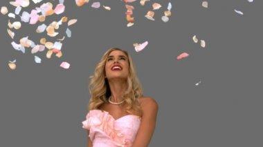 Woman in ballgown admiring petals falling on grey screen — Stockvideo