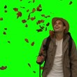 Cheerful mstanding under leaves falling on green screen — Stock Video #29490183