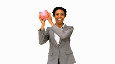Businesswoman listening to a full piggy bank on white screen — Stock Video