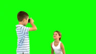 Brother taking pictures of his sister jumping on green screen — Stock Video