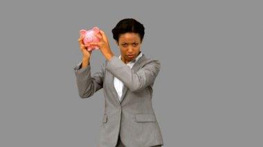 Businesswoman listening to an empty piggy bank on grey screen — Stock Video