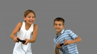 Siblings playing video games on grey screen — Stock Video