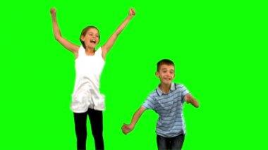 Siblings jumping together on green screen — Stock Video