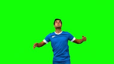Handsome man controlling a football with his chest on green screen — Stock Video
