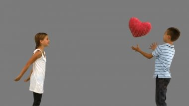 Siblings playing with a heart shaped cushion on grey screen — Stock Video