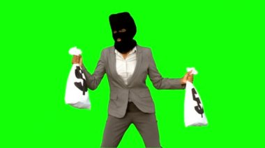 Burglar wearing balaclava and holding money bags on green screen — Stock Video
